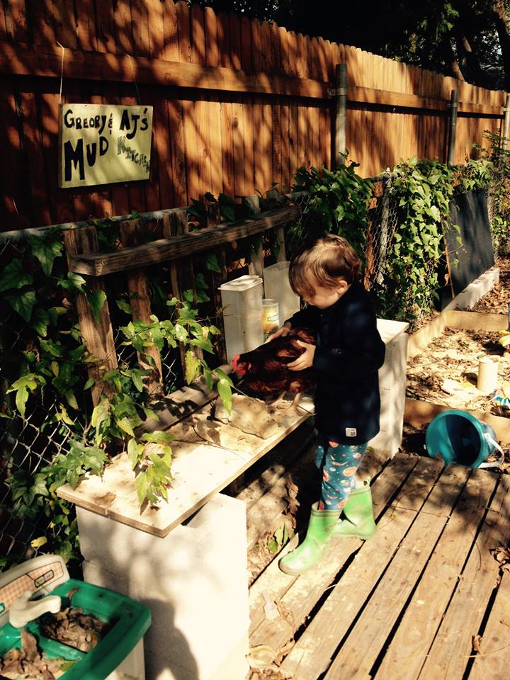 Gregory with chicken in mud kitchen